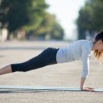 Yoga in the city: beautiful young sporty woman wearing sportswear working out on the street on summer day, doing plank posture, exercises for abs muscles, full length, side view